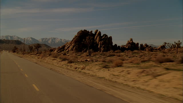 rear pov driving down a desert highway with mountains and rocky outcroppings - moving process plate stock videos and b-roll footage