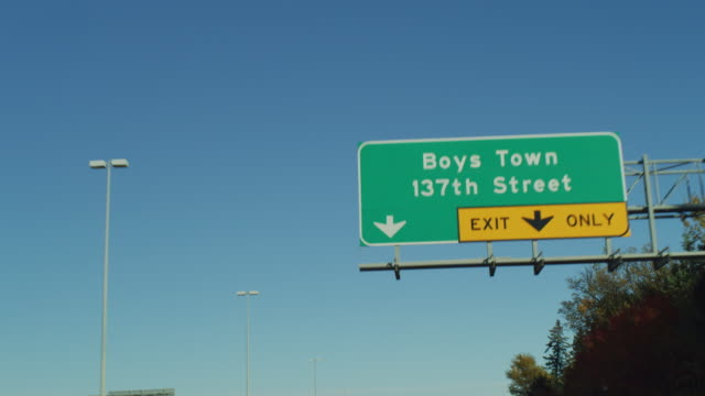 """pov driving down a highway expressway under a green sign """"boys town. 137th street exit only."""" - only boys stock videos & royalty-free footage"""