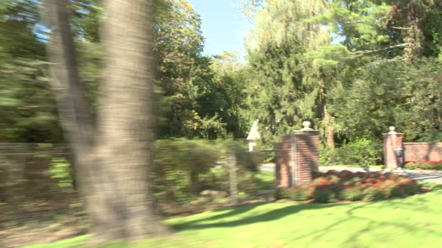 rpov driving down a tree-lined street, passing lush greenery and white picket fencing / united states - picket fence stock videos & royalty-free footage