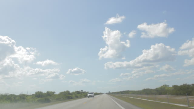 Driving down an open highway on a sunny day with fluffy clouds