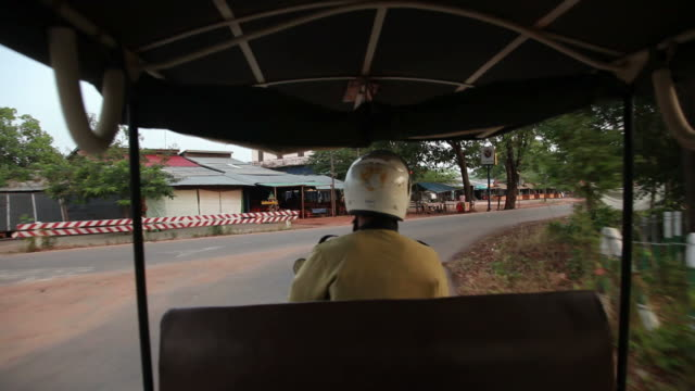 pov ws driving down cambodian town street / angkor wat, siem reap, cambodia - risciò a motore video stock e b–roll