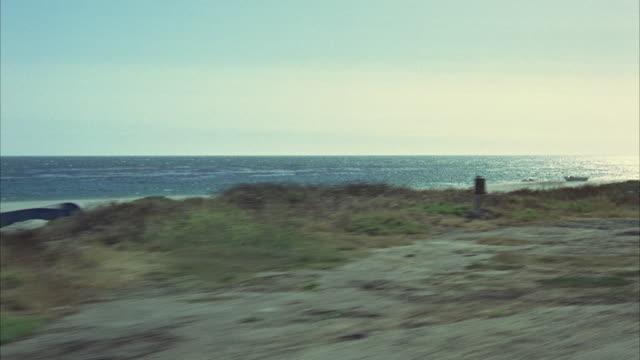 vídeos de stock, filmes e b-roll de 1965 rear pov driving down coastal road - cerca