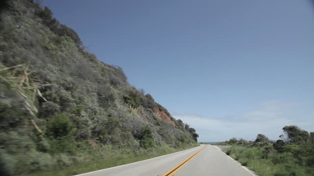 POV driving down Highway 1 with the Paciic Ocean in the background in Big Sur