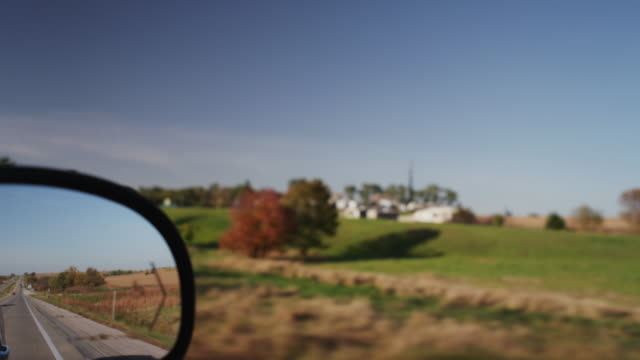 driving down interstate i-80, rear view mirror of country side passing by. - アイオワ州点の映像素材/bロール