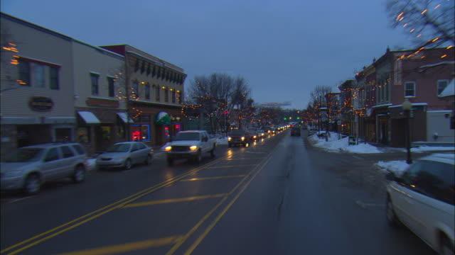 POV Driving down main street at dusk in Winter, Milford, Michigan, USA