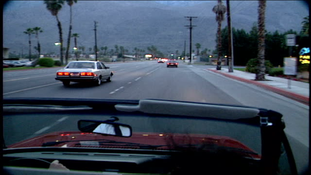 pov of driving down road in palm springs from topless car - cabrio stock-videos und b-roll-filmmaterial