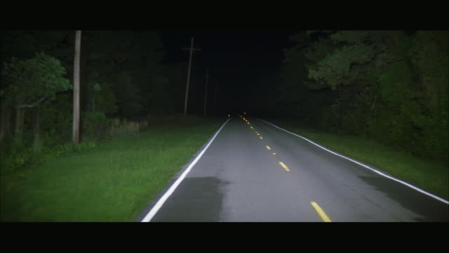 rear pov driving down rural two lane highway at night - moving process plate stock videos and b-roll footage