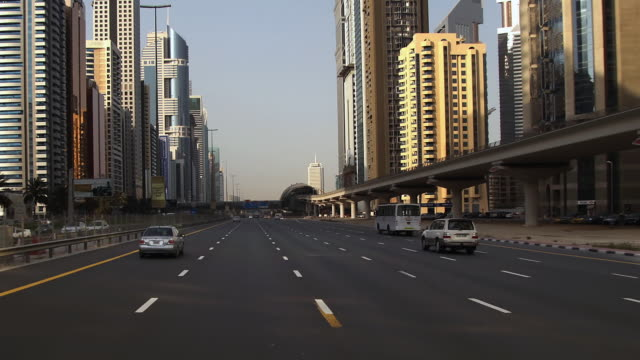 vídeos de stock, filmes e b-roll de t/l driving down sheikh zayed road with high-rise buildings on either side / dubai, united arab emirates - formato letterbox