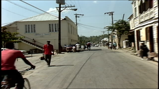 vidéos et rushes de driving down street past people and bike riders in jamaica - 1980 1989