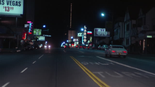 WS REAR POV Driving down Sunset Blvd at night / Los Angeles, California, USA