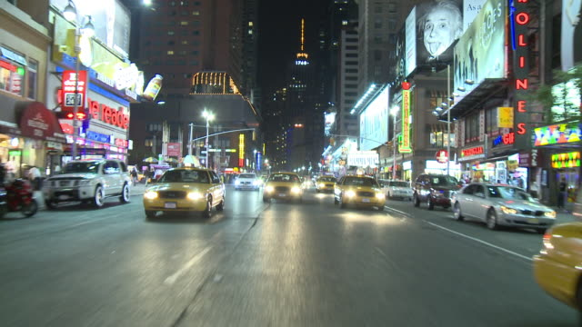 RPOV Driving down the brightly lit Broadway after dark, passing theaters, restaurants and storefronts / New York City, New York, United States