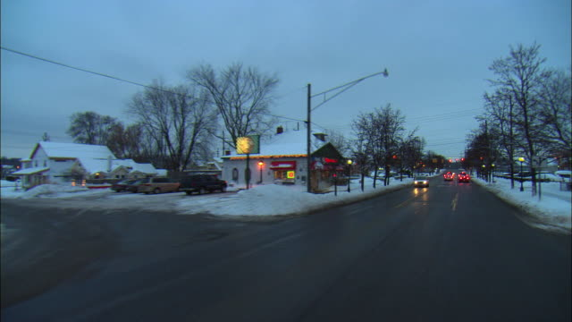 POV Driving down town street at dusk in Winter, Milford, Michigan, USA