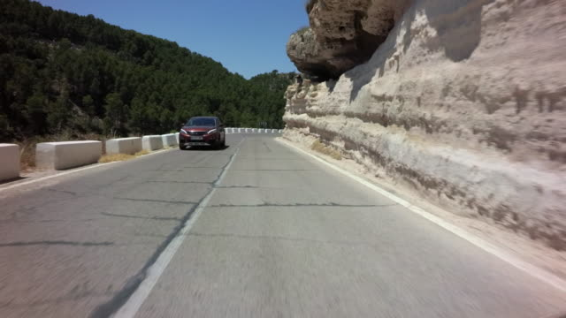 pov driving down winding country highway with crash barriers and erosive rock formations - kurvenreiche straße stock-videos und b-roll-filmmaterial
