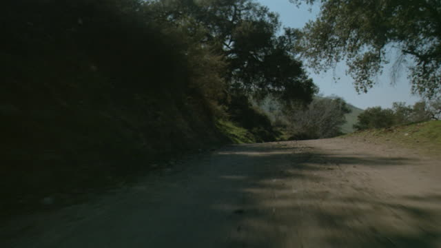stockvideo's en b-roll-footage met car pov driving fast down rural dirt road - grind