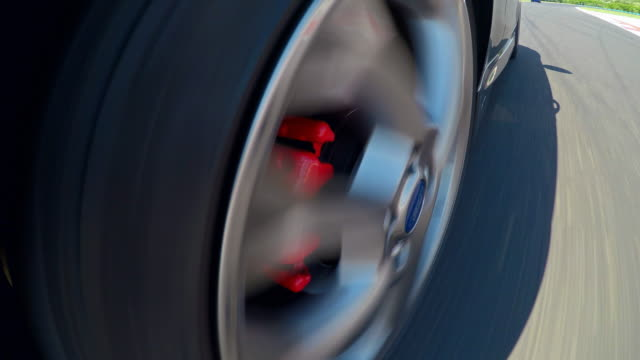 Driving fast on a race track, view of the cars spinning tire