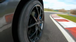 Driving fast on a race track, view of the cars spinning wheel