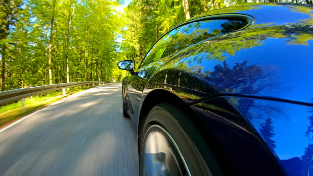 driving fast with a sports car on a winding country road surrounded by lush foliage - tire vehicle part stock videos & royalty-free footage