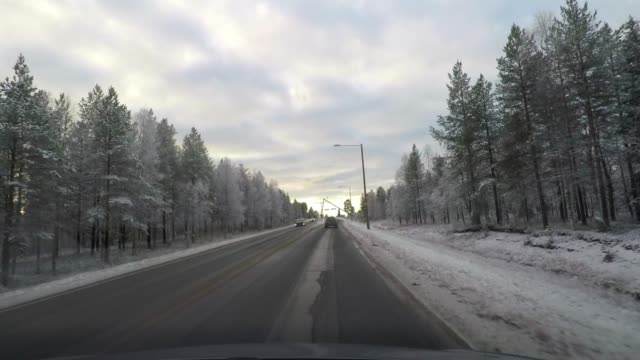 driving from the arctic circle along highway through snow covered forest, road trip in finland - car point of view stock videos & royalty-free footage