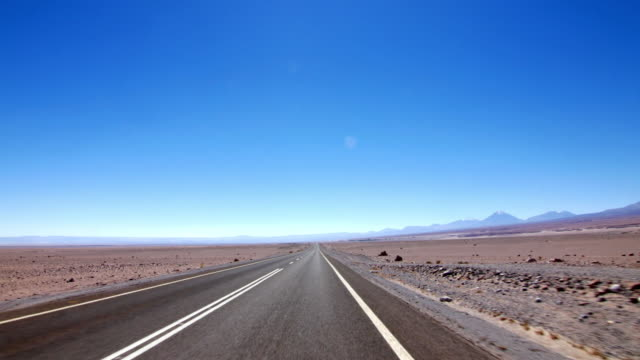 driving in a long straight asphalt road in the desert - car point of view stock videos & royalty-free footage