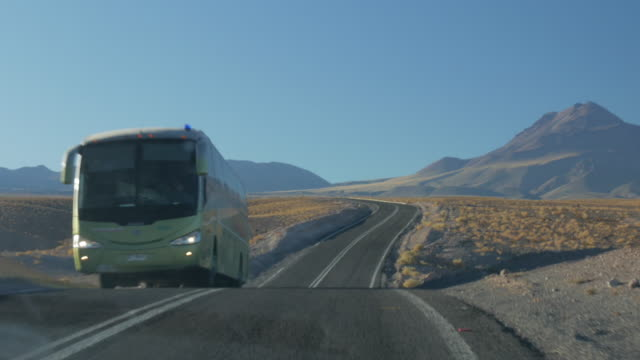 driving in a road in atacama desert and a bus crossing in opposite direction - südamerika stock-videos und b-roll-filmmaterial
