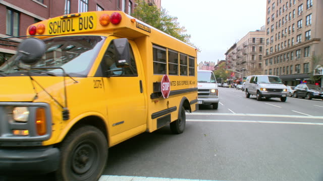 DS Driving in an Upper West Side mixed use area, past school buses, pedestrians at crosswalks, and mid-rise buildings / New York City, New York, United States