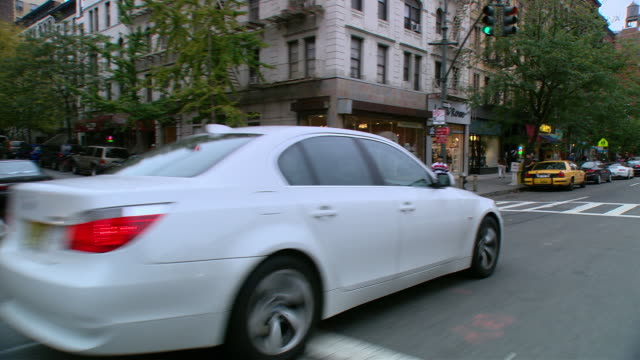 DS Driving in an Upper West Side mixed use area, with parked vehicles, storefronts, and townhouses / New York City, New York, United States