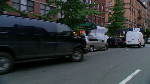 ds driving in an upper west side mixed use area, with parked vehicles, storefronts, and townhouses / new york city, new york, united states - ladenschild stock-videos und b-roll-filmmaterial