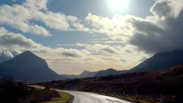 driving in europe with silhouette montain range and dramatic sky - skye stock videos and b-roll footage