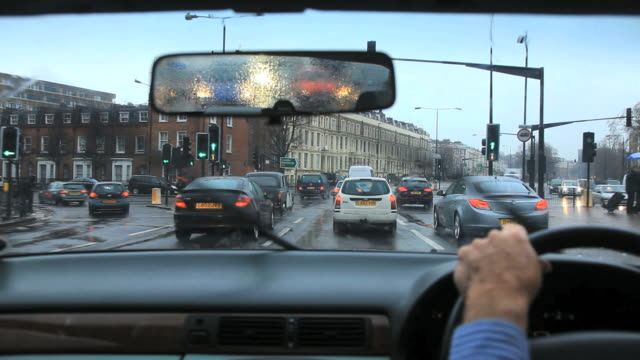 driving in kensington on a rainy wet day with busy traffic  in london - kensington und chelsea stock-videos und b-roll-filmmaterial