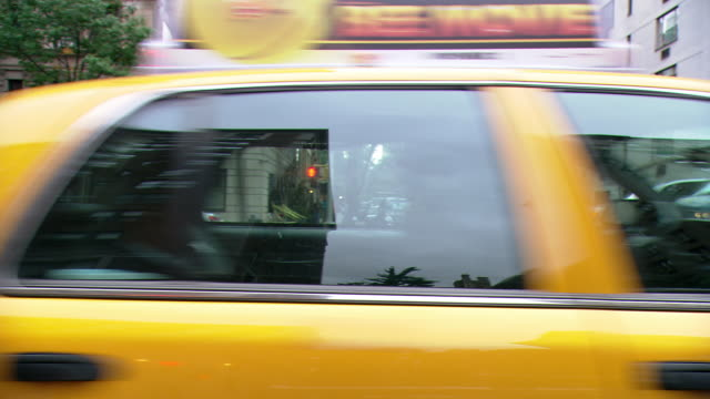 ds driving in midtown manhattan, cruising past apartment buildings and taxis on a divided avenue / new york city, new york, united states - yellow taxi video stock e b–roll