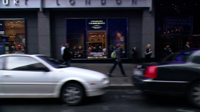 DS Driving in Midtown Manhattan, passing a retail shopping area crowded with parked vehicles, traffic, and pedestrians on crosswalks and sidewalks / New York City, New York, United States