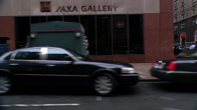 DS Driving in Midtown Manhattan, passing parked vehicles, an intersection, storefronts, a gallery, and pedestrians on sidewalks and crosswalks / New York City, New York, United States