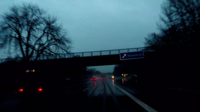 driving in rain at night on highway through a dark forest, germany, europe - high point video stock e b–roll