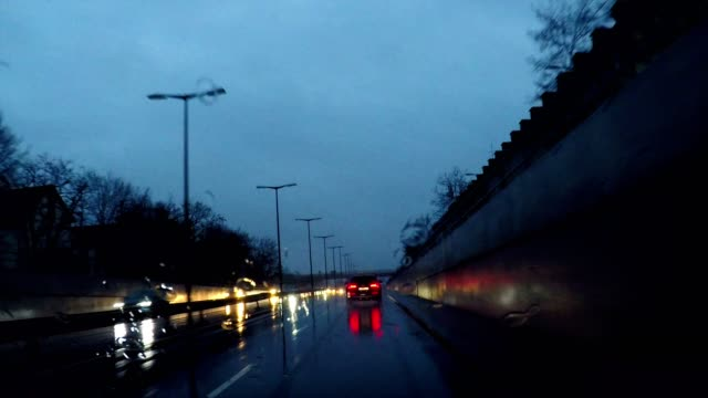 driving in rain at night through outer suburbs of munich, germany, europe - high point video stock e b–roll