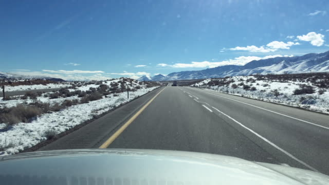 pov of driving in the mountains in winter with snow. - goodsportvideo stock videos and b-roll footage