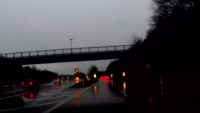driving in the rain at night through dark forest, exiting highway towards munich, germany - high point video stock e b–roll