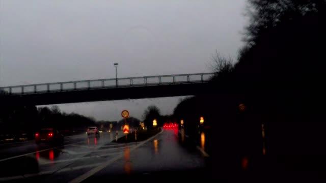 driving in the rain at night through dark forest, exiting highway towards munich, germany - verkehrsschild stock-videos und b-roll-filmmaterial