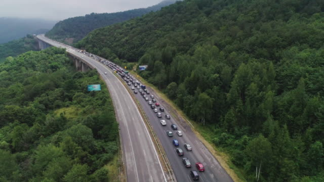 driving in the rush hour through a traffic jam. aerial view of a highway bridge with a big traffic jam at the entrance of a capital city during covid-19 pandemic. busy life, top view, cityscape. - transportation event stock videos & royalty-free footage