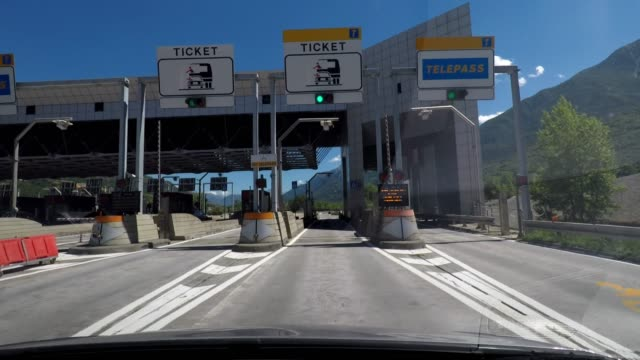 driving into a highway toll booth, stopping, paying and driving off, car travel, road trip in italy - segnaletica stradale video stock e b–roll