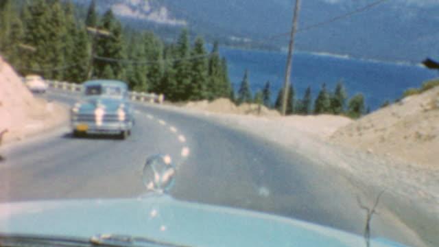 driving into tahoe / romantic pier and lake shots / playing ping pong / driving / lake tahoe visit on july 01, 1968 in carson city, nevada - キャデラック点の映像素材/bロール