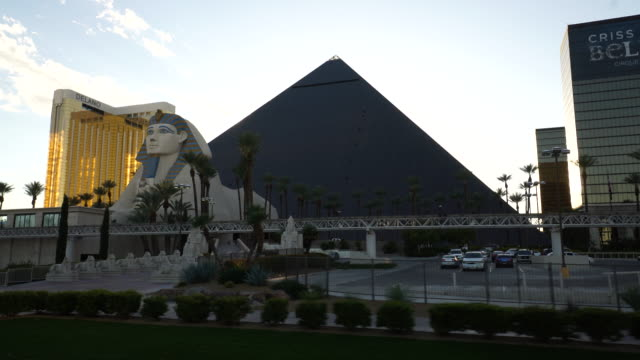 Driving POV of Las Vegas strip featuring the Luxor hotel at sunset