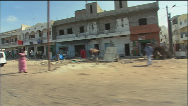 pov driving on a dirt road through a village / africa - centro commerciale suburbano video stock e b–roll
