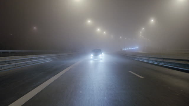 DS Driving on a foggy, wet night past billboards and open space, other cars passing