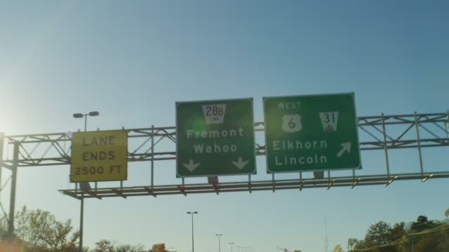 """pov driving on a highway expressway under a green sign with directional arrows """"lane ends 2500 ft fremont wahoo highway 6 west 31 elkhorn lincoln."""" - elkhorn nebraska stock videos & royalty-free footage"""