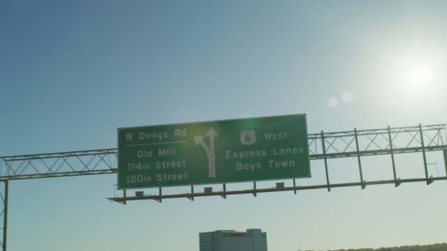 """pov driving on a highway expressway under a green sign with directional arrows """"w dodge rd old mill 114th street 120th street highway 6 express lanes west boys town."""" - directional sign stock videos & royalty-free footage"""