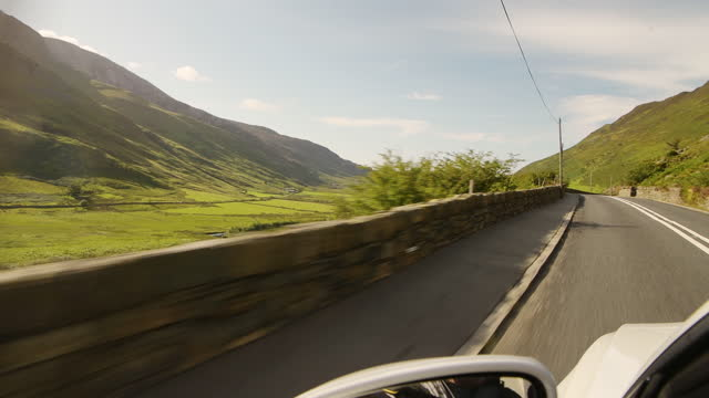 driving on a long concrete road passing by the lush green mountains landscape during sunset in snowdonia national park in wales - long shot - road stock videos & royalty-free footage