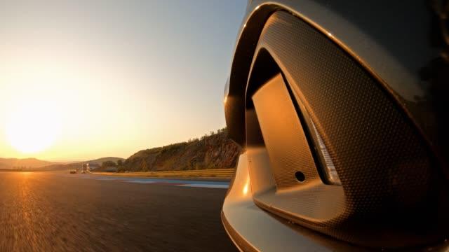 vídeos y material grabado en eventos de stock de conduciendo en una pista de carreras al atardecer, cruzando la línea de meta - coche deportivo