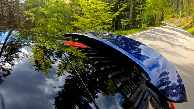 driving on a scenic winding road surrounded by green trees, view of rear windshield, tail lights and spoiler - windscreen stock videos & royalty-free footage