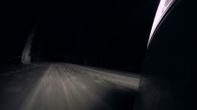 Rijden op een besneeuwde landweg 's nachts