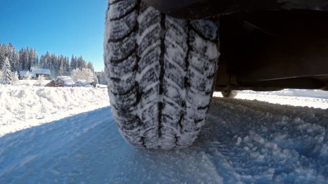 driving on a snowy single lane winter forest road - tyre stock videos & royalty-free footage